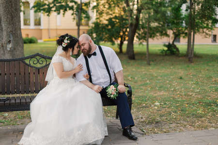 Newlyweds sit on a bench in the park.