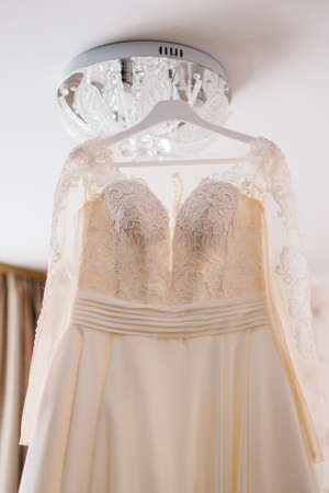 Very beautiful wedding dress of the bride hanging on the chandelier in the room.