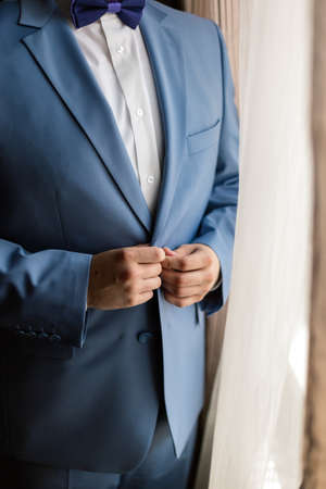 the man zips up his jacket, groom in a jacket, white tie, bridegrooms fees, business style. Banque d'images
