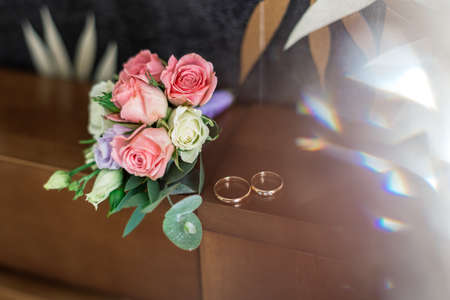 Wedding bouquet and rings illuminated by photo with light.