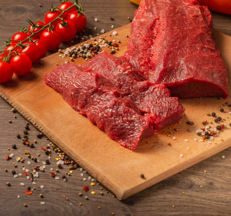 Raw beef on a wooden background with spices and vegetables.