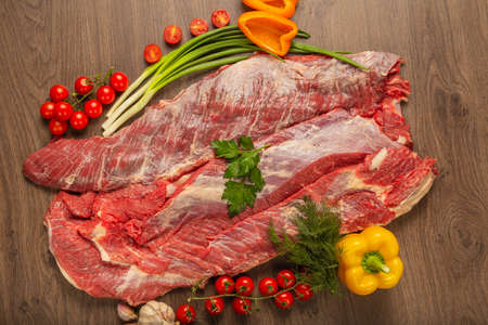 Raw beef on a wooden background with spices and vegetables. Standard-Bild - 118831697