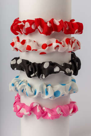 Colored bright childrens hair ties on a white background.