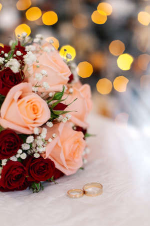 Beautiful fresh wedding bouquet with rings on a white bed.