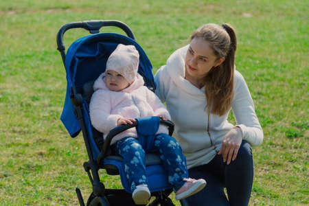 Young mother with a baby in a stroller in a summer park. Stock Photo