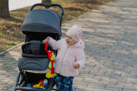 A little girl is rolling baby carriage in the park. Child in the park playing with pram. Stock Photo