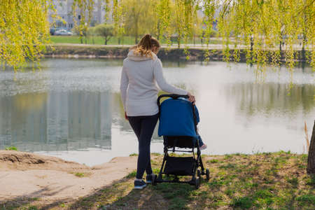 Young mother with a baby in a stroller by the lake in summer. Stock Photo