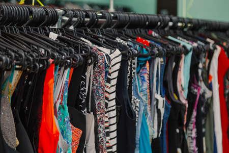 Kleurrijke kleding op hangers in een winkel.