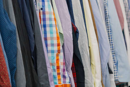 Colorful clothes on hangers in a store.