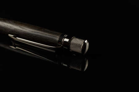 Beautiful handmade pen on a black mirror background.
