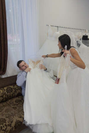Beautiful man and woman in a wedding salon. woman throws wedding dresses to man.