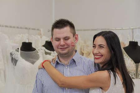 Beautiful woman in a wedding dress hugs her man in a wedding salon.