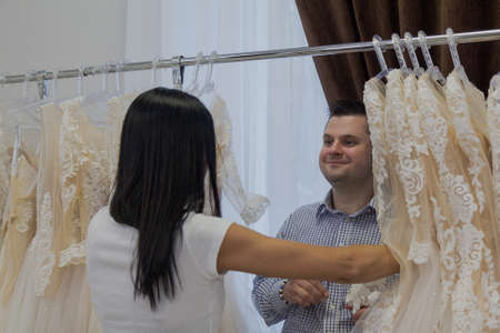 Young man shows a ring to a woman hiding in wedding dresses in a bridal salon.