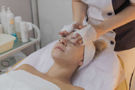 Professional beautician does the procedure for a woman in a beauty parlor. Stok Fotoğraf
