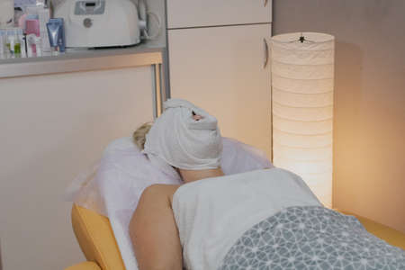Woman lying on a couch in a beauty parlor with a closed face to absorb cream.