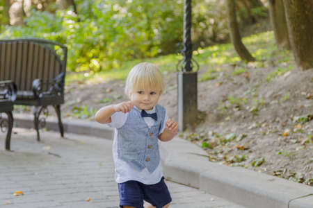Little boy runs on the asphalt in the park. Zdjęcie Seryjne