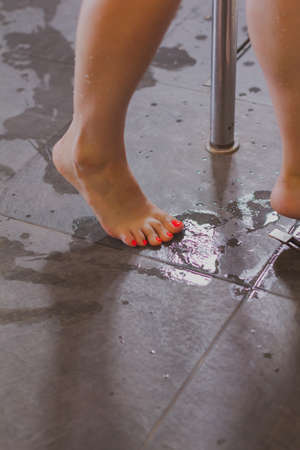 Feet of a girl with manicure on a wet tile.