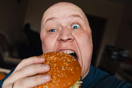 The eating of a hamburger by a man with a terrible expression Zdjęcie Seryjne