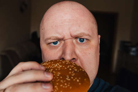 The eating of a hamburger by a man with a terrible expression Archivio Fotografico - 132203045