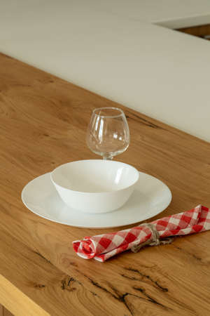 A plate and a glass on a kitchen wooden table