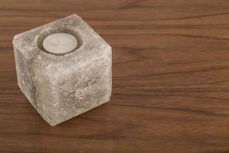 Candlestick made of natural salt on varnished coating, reflection of objects.