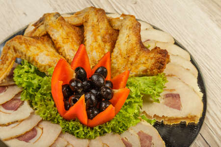 Dish from tartlets chicken wings and meat sliced with the presence of lettuce leaves Stock Photo