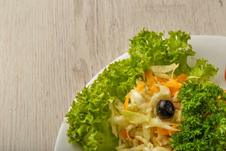 Fresh cabbage salad with greens on a plate.