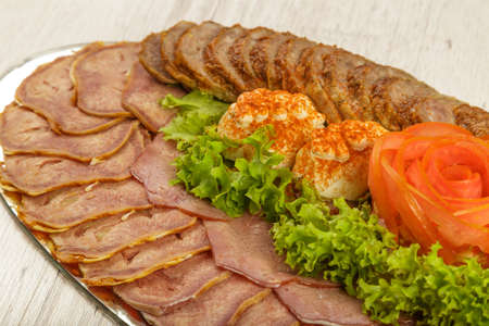 Meat sliced on a mirror dish decorated with verdure.