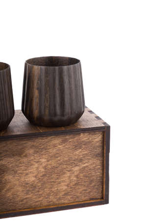 Beautiful wooden mugs on a wooden box. White isolated background. Imagens
