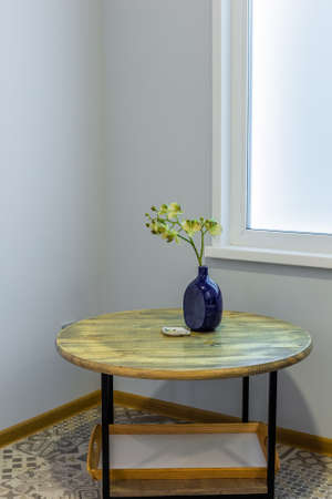Blue vase on a wooden table in a modern interior interior. Archivio Fotografico - 134555572