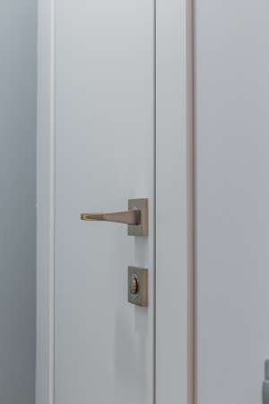Modern metal door handle on a white door. Archivio Fotografico - 134555577