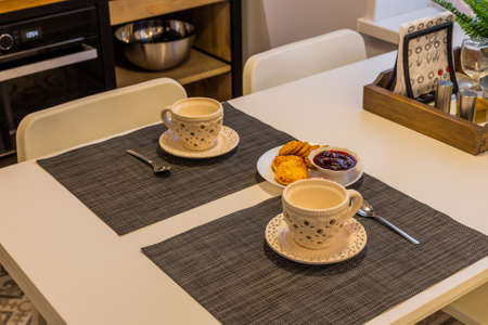 Modern kitchen table with tea and cookies. Archivio Fotografico - 134555587
