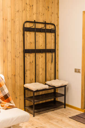 Iron shoe rack with clothes hooks at the front door. Archivio Fotografico - 134555548