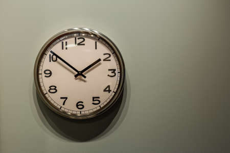 Modern quartz clock on a painted wall. Archivio Fotografico - 134555560