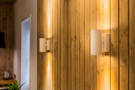 Modern lamps on a wooden wall in the interior of the house. Archivio Fotografico - 134555561