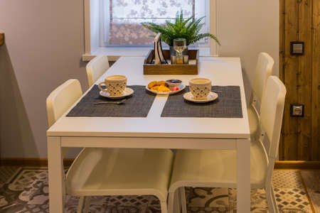 Modern kitchen table with tea and cookies. Archivio Fotografico - 134555514