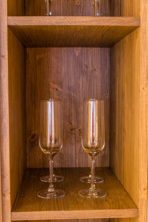 Glass wine glasses on a wooden shelf. Archivio Fotografico - 134555451