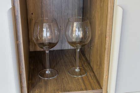 Glass wine glasses on a wooden shelf. Archivio Fotografico - 134555455