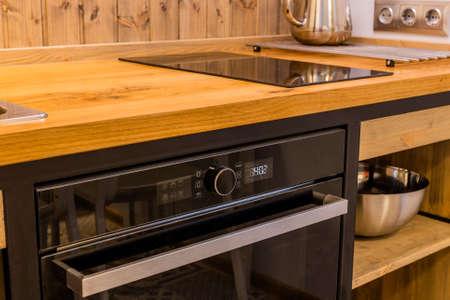 Black modern stove in a wooden kitchen. Archivio Fotografico - 134555457