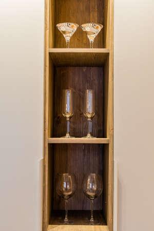 Glass wine glasses on a wooden shelf. Archivio Fotografico - 134555465