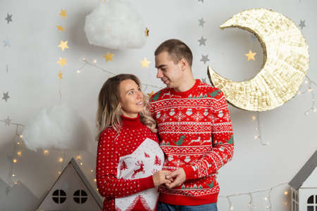Beautiful happy couple in love in the Christmas decor for Christmas night. Happy Merry Christmas 2020.