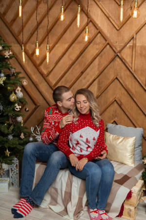Beautiful happy couple in love in the Christmas decor for Christmas night. Happy Merry Christmas 2020 Stock Photo