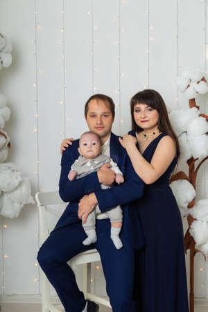 Beautiful happy family in a bright photo area.