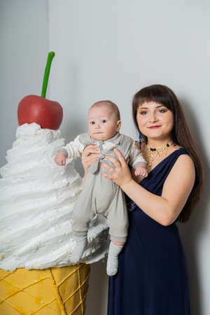 Happy mother in evening dress with a child in a photo studio. Stock fotó