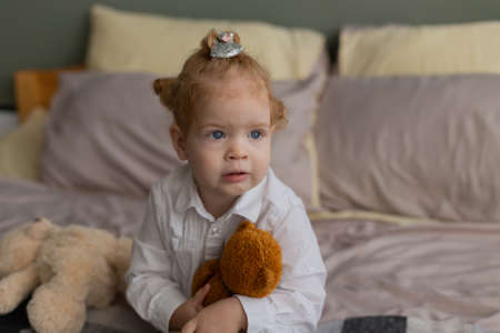 Beautiful little girl on the bed plays with plush toys. Banque d'images