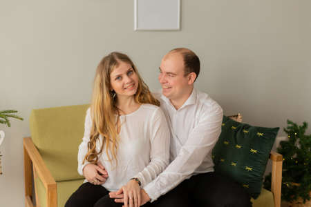 Beautiful happy lovers on a modern sofa in a beautiful interior. Stock fotó