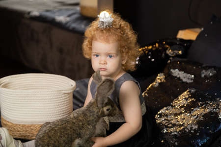 Beautiful little girl child on a New Years bed with an artificial rabbit. Archivio Fotografico - 135866630