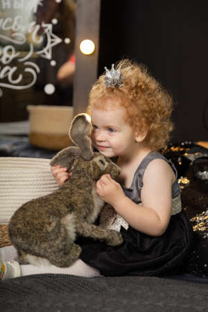 Beautiful little girl child on a New Years bed with an artificial rabbit. Archivio Fotografico - 135866633