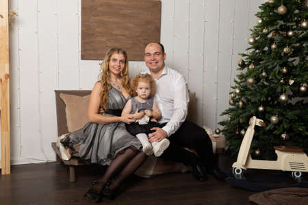 Beautiful young happy family with a child on New Years Eve on the couch. New Year 2020. Archivio Fotografico - 135866655