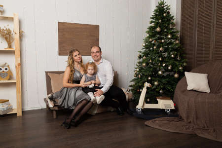 Beautiful young happy family with a child on New Years Eve on the couch. New Year 2020. Archivio Fotografico - 135866658